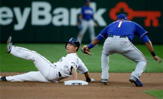 Seattle Mariners Norichika Aoki, left, is caught stealing second base by Texas Rangers shortstop Elvis Andrus (1) in the first inning of a baseball game, Monday, April 11, 2016, in Seattle. (AP Photo/Ted S. Warren)
